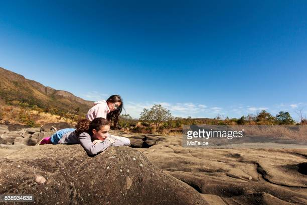 Sisters resting over a rock on Vale da Lua (Moon Valley)