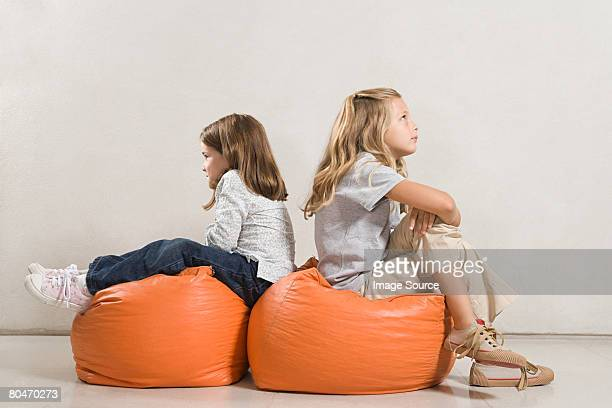 Sisters sat back to back on beanbags