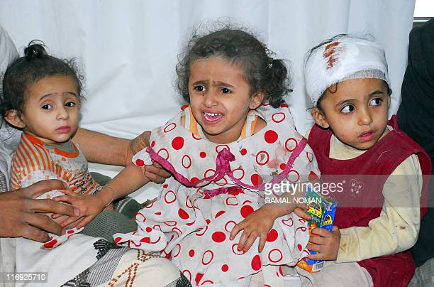 Sisters sit on a hospital bed after their house was hit as fighting rages in the alHasaba neighbourhood north of the capital Sanaa on May 24 2011...