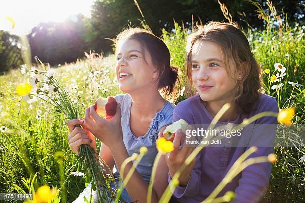 Sisters sitting in field eating apples