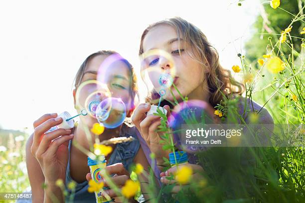 Sisters sitting in field of flower blowing bubbles