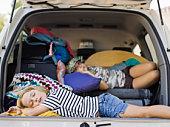 Sisters sleeping in minivan hatchback