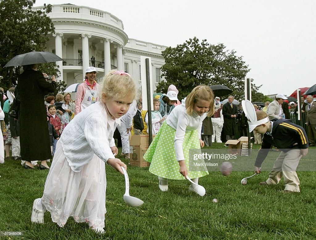 Sisters Sophie Darrow and Jordan Darrow use large spoons to roll eggs after US President George W Bush blew a whistle to start the Easter egg roll on...