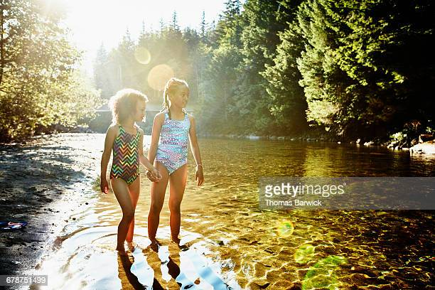 Sisters standing in river holding hands