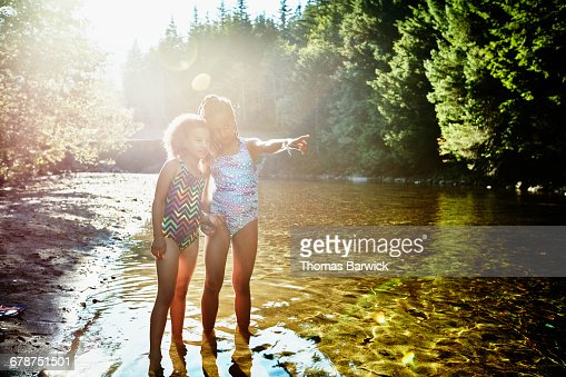 Sisters standing in river pointing upstream