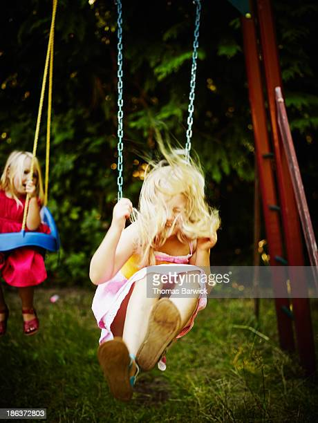 Sisters swinging together on swing set