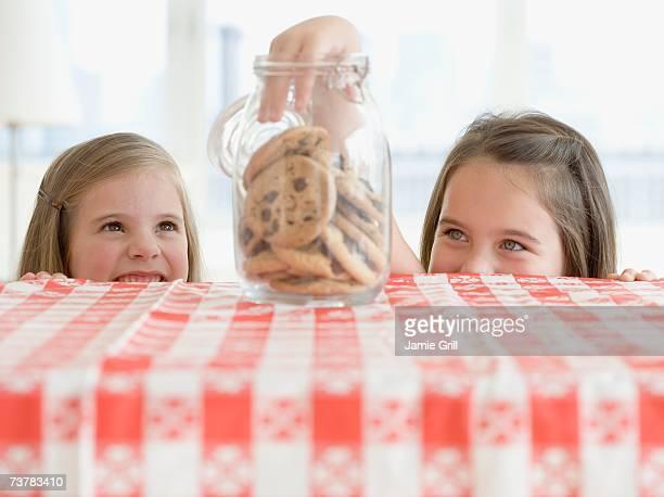Sisters taking cookies from jar