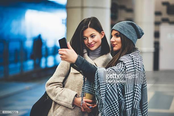 sisters taking selfie in station