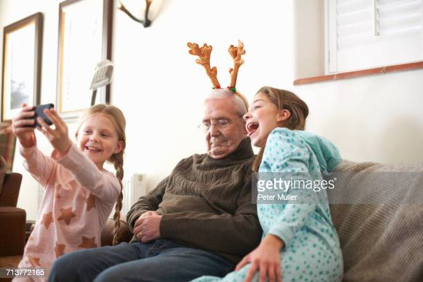 Sisters taking smartphone selfie of sleeping grandfather in reindeer antlers