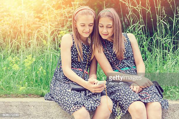 Sisters texting on smartphone among nature