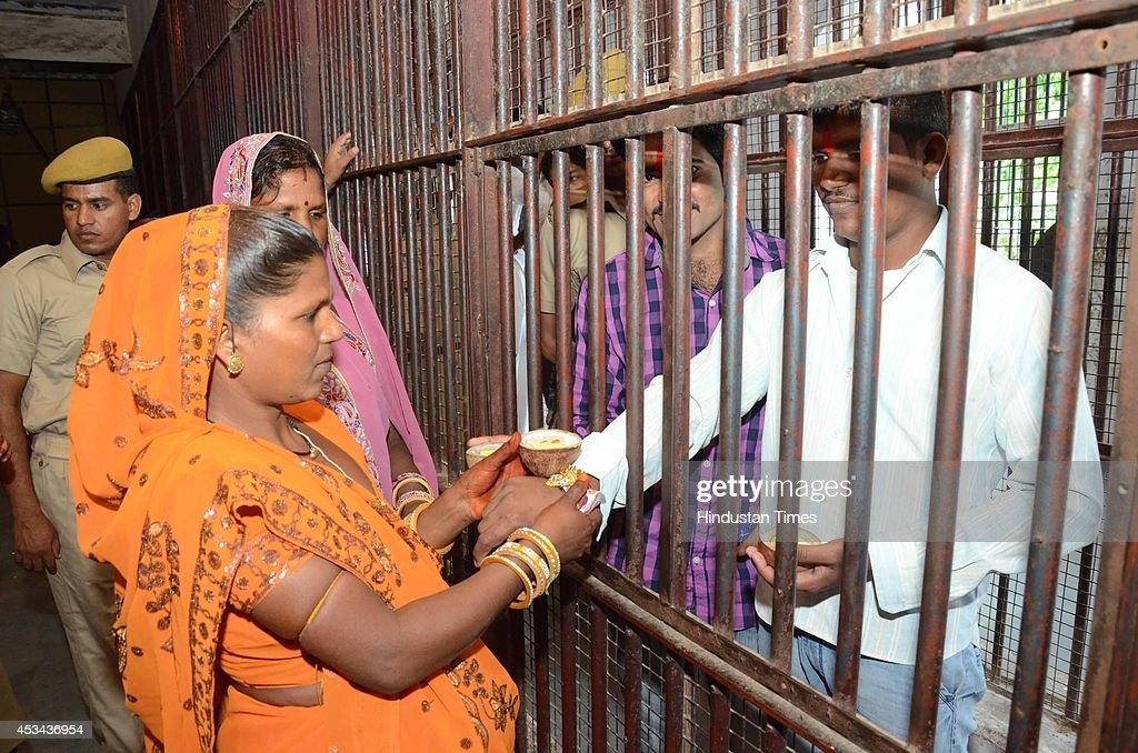 Sisters tie rakhi on the wrist of their imprisoned brothers on the occassion of Raksha Bandhan, outside Central jail on August 10, 2014 in Jaipur, India. The festival of Raksha Bandhan' or 'Rakhi' celebrate the brother-sister love. Sisters tie sacred Rakhi string on their brothers' right wrists and pray for their protection.