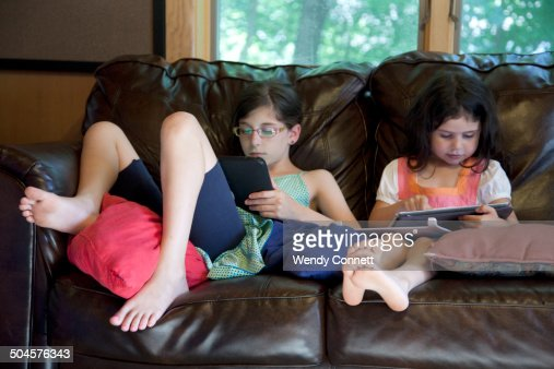 Sisters using electronic tablets