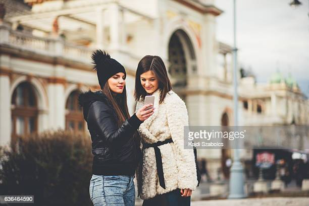 sisters using pshone in Budapest