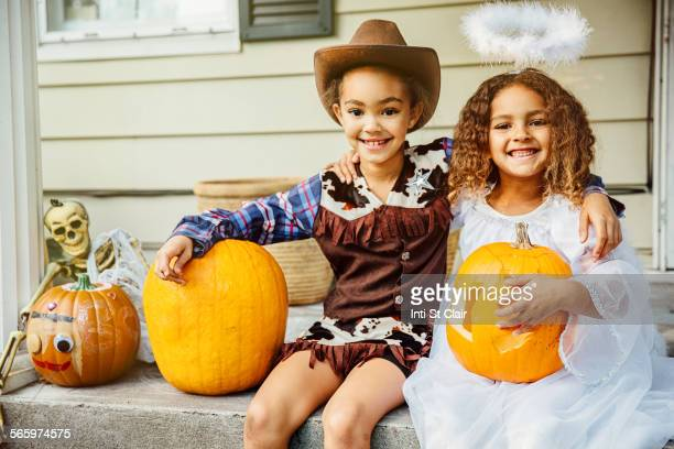 Sisters wearing Halloween costumes with jack-o-lanterns on porch