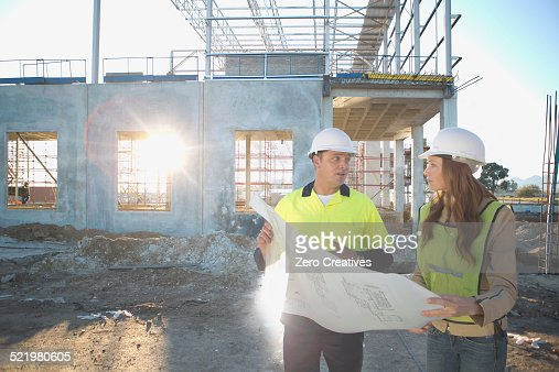 Site manager and architect chatting about blueprint on construction site