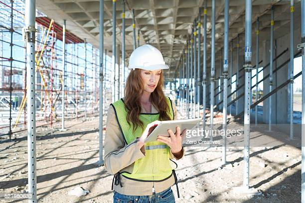 Site manager using touchscreen on digital tablet on construction site