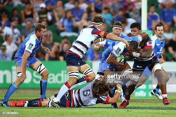 Sitiveni Mafi of the Force gets tackled by Jordy Reid Luke Jones and Lopeti Timpani of the Rebels during the round one Super Rugby match between the...
