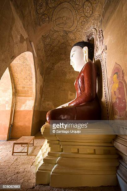Sitting Buddha colored statue on a temple