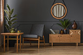 Sitting corner with wooden table, green cup and pot in a grey room interior with mirror and cabinet