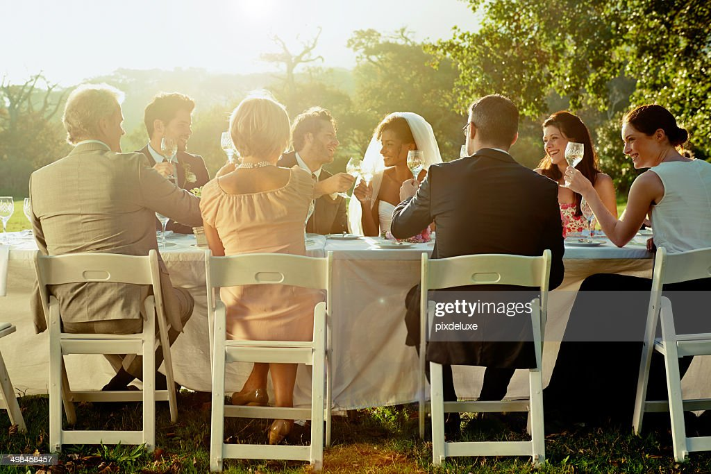 Sitting down to a table of friends and family : Stock Photo
