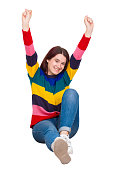 Cheerful excited young woman raising bands up sitting on the floor happy emotion isolated over white background.