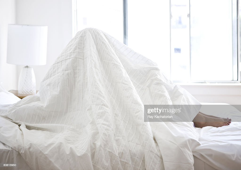 sitting in bed sheets over head horizontal