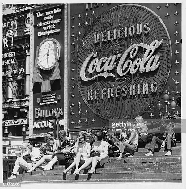 Sitting in front of huge neon advertisements on the steps of the Eros fountain at Piccadilly Circus London in the 1960s