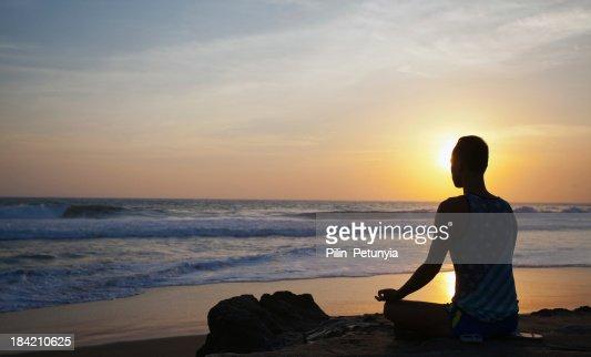 sitting man doing yoga on shore of ocean : Stock Photo