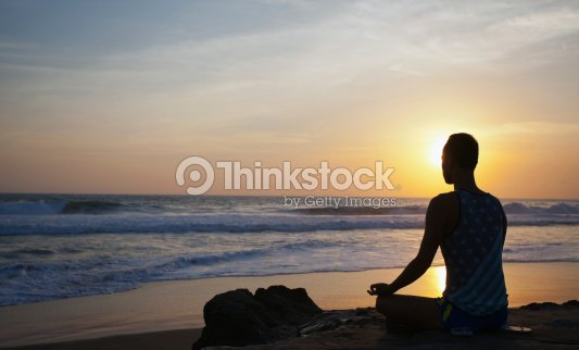 sitting man doing yoga on shore of ocean : Stock Photo