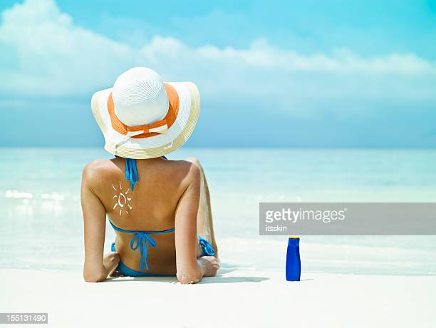 Sitting near the ocean with sunscreen bottle