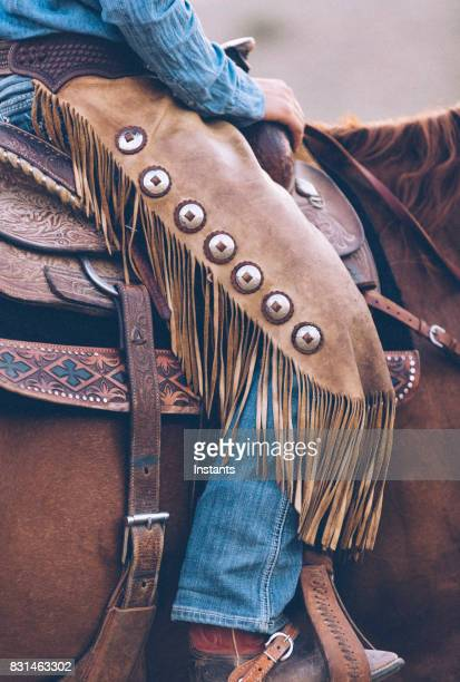 Sitting on a saddle, a close look at a cowgirl's attire with the leather chaps, denim and boots.