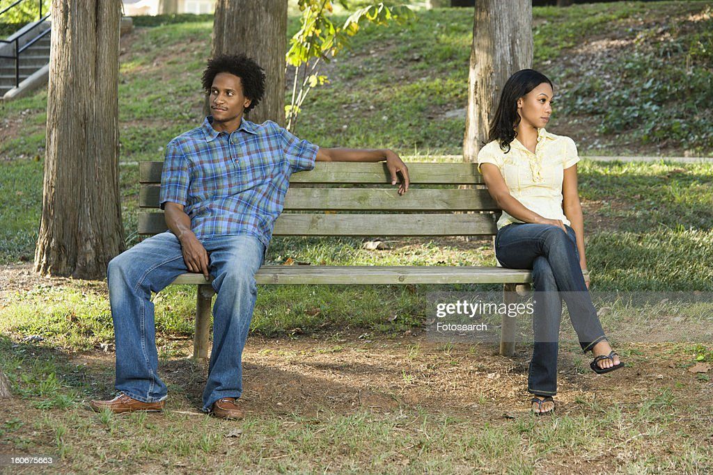 Sitting on opposite sides of park bench : Stock Photo
