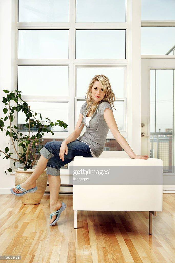 Sitting on sofa, smiling : Stock Photo
