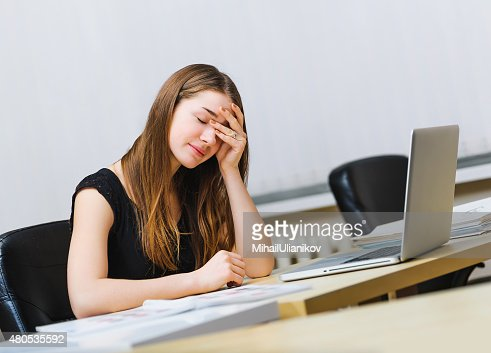 sitting pensive tired woman working of notebook computer : Stock Photo