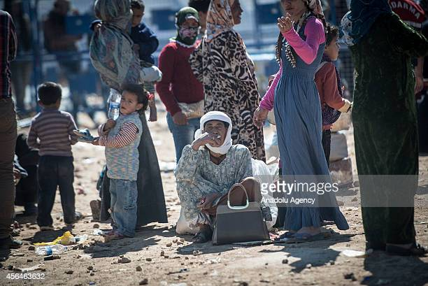 A sitting Syrian Kurdish old woman looks around as a group of SyrianKurds fled from the clashes between Islamic State of Iraq and the Levant and...
