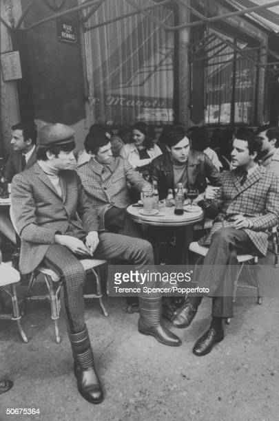 Sitting together at a table located inside of the Les Deux wearing mod clothes are models Michel Marchand Richard Faust Alain Debnet and Edmond...