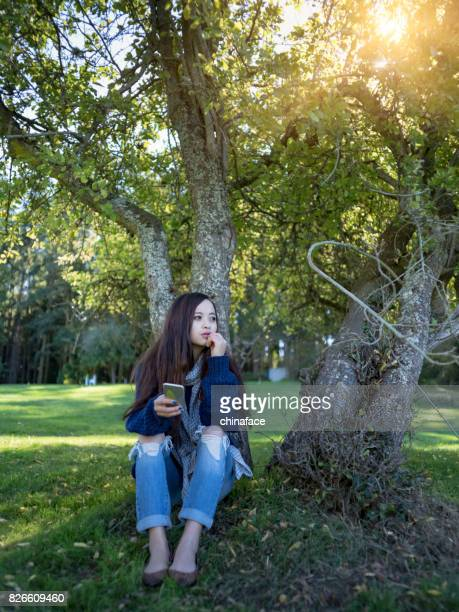 sitting under a tree with holding smartphone