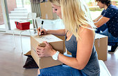 Sitting woman labeling moving boxes while her husband prepares boxes