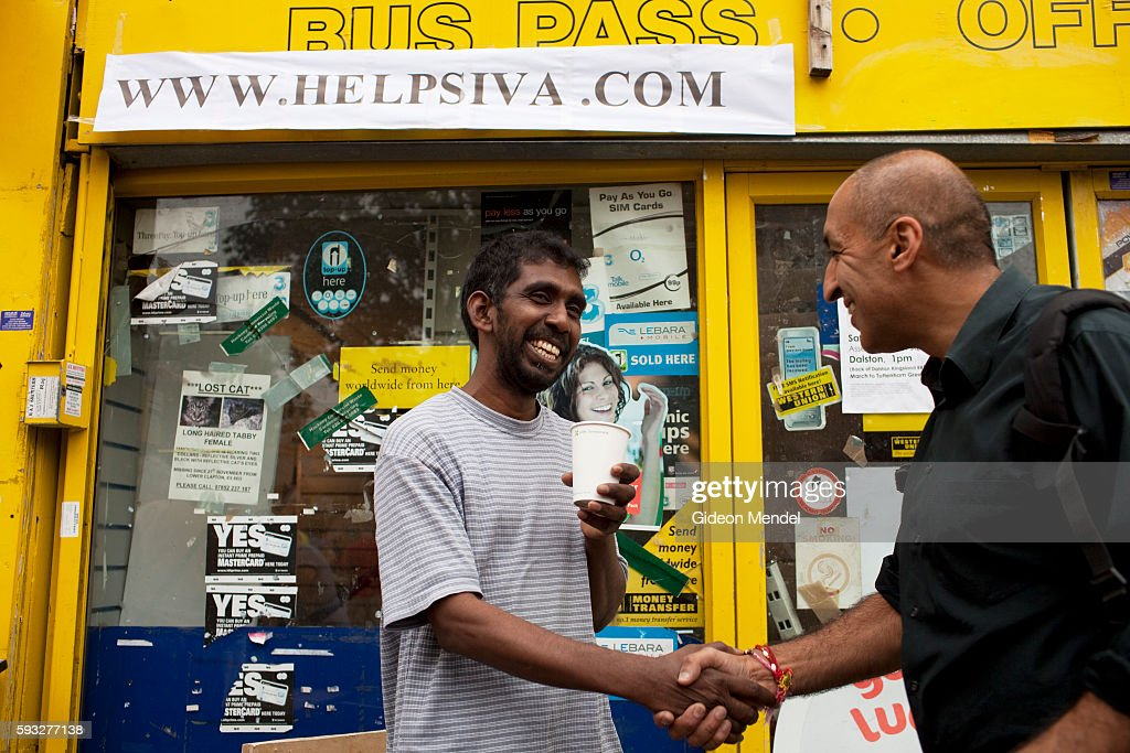 Siva Kandia gereets a wellwisher outside his shop on Clarence Road in Hackney during a community tea party held exactly a week after the violent...