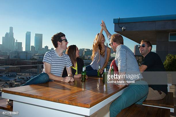 Six adult friends drinking beer at table of rooftop bar with Los Angeles skyline, USA