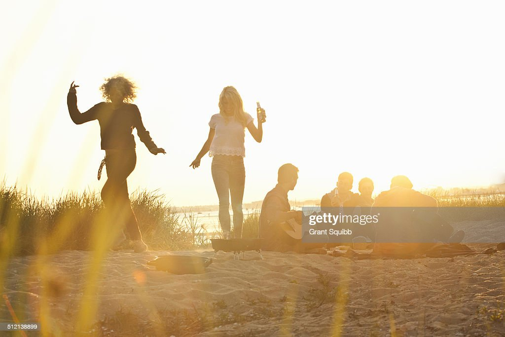 Six adult friends partying at sunset on Bournemouth beach, Dorset, UK