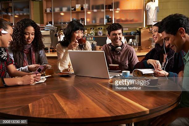 Six adults sitting at table in cafe, talking and laughing