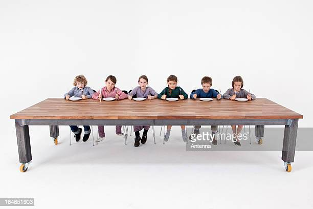 Six angry kids holding knives and forks impatiently waiting for food