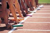 Six Athletes Holding Batons at the Starting Line of a Relay Race