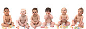 Six cute babies in diapers sitting in a row, playing with blocks. White background. One baby is wearing hearing aids.