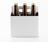 Six beer bottles in cardboard container with gold caps with side of carrier facing camera