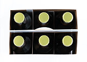 Pattern of six beer bottles in cardboard container with gold caps facing upwards