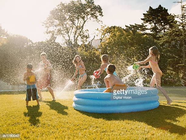 Six Children Have a Water Fight Round a Paddling Pool in a Back Garden