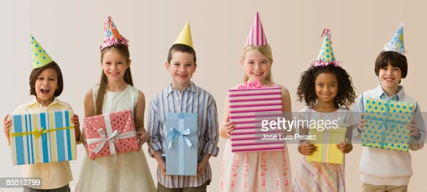 Six children holding up birthday presents  : ストックフォト