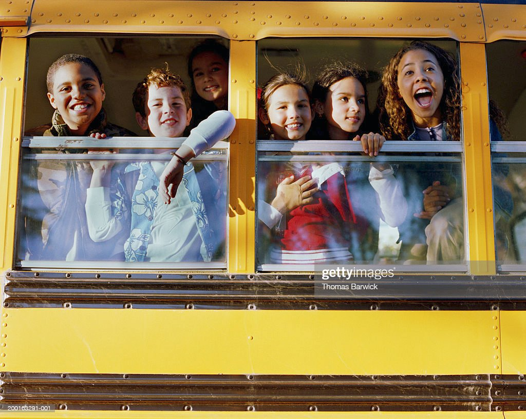 Six children (8-10) looking out windows on school bus, low angle view